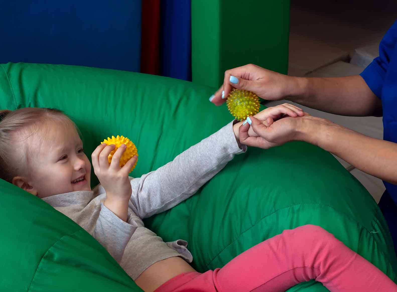 girl in beanbag with teacher rolling textured ball text touch sense