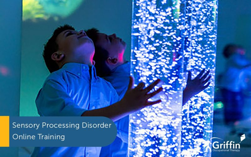 boy standing at a blue bubble tube text online sensory training