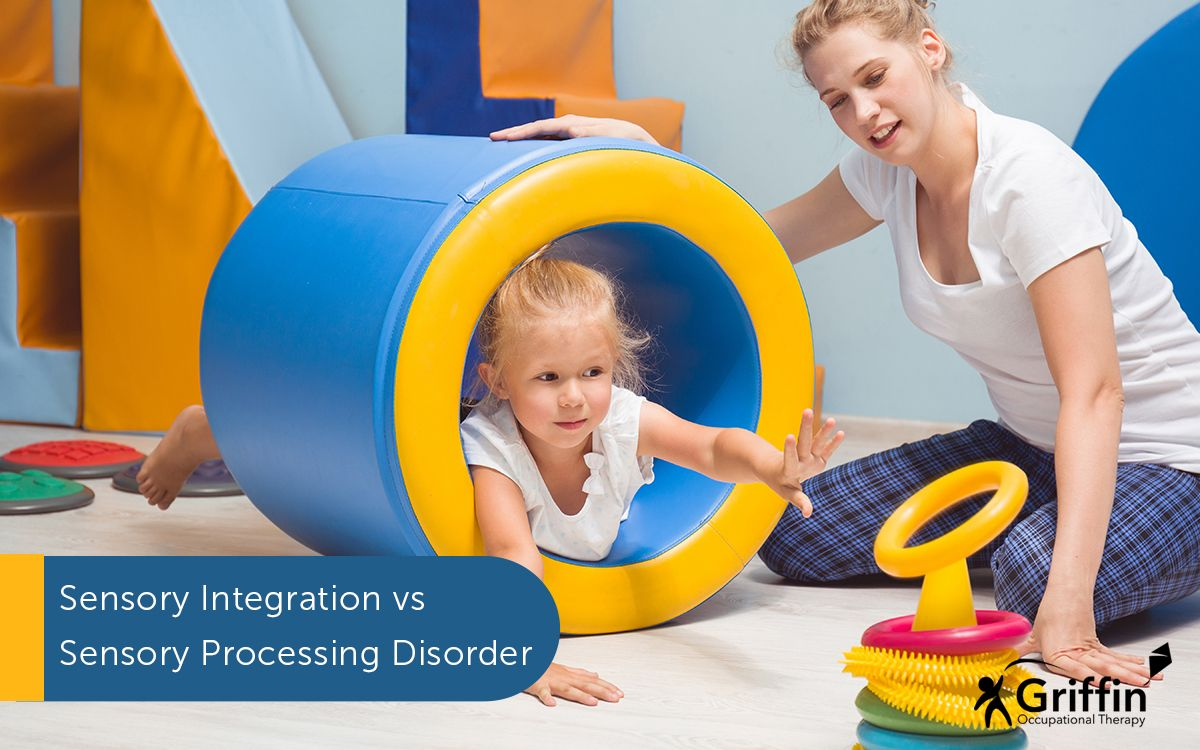 a child in a barrel throwing rings over a cone with therapist holding the barrel text What's the difference between sensory integration and sensory processing disorder