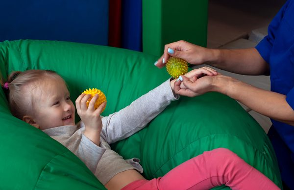 child lying in beanbag with teacher rolling sensory ball on her arm