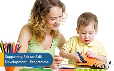 mother sitting with child who is cutting text supporting scissor skill development