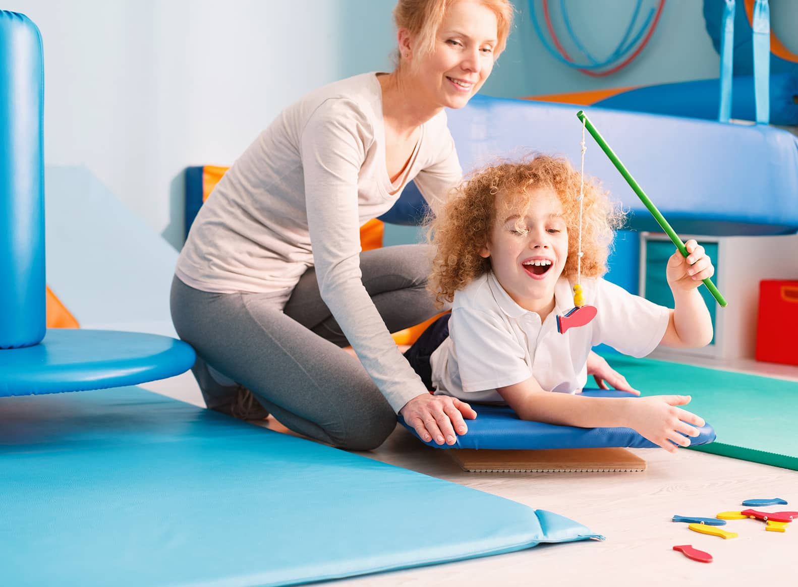 occupational therapist supporting child on a wobble board