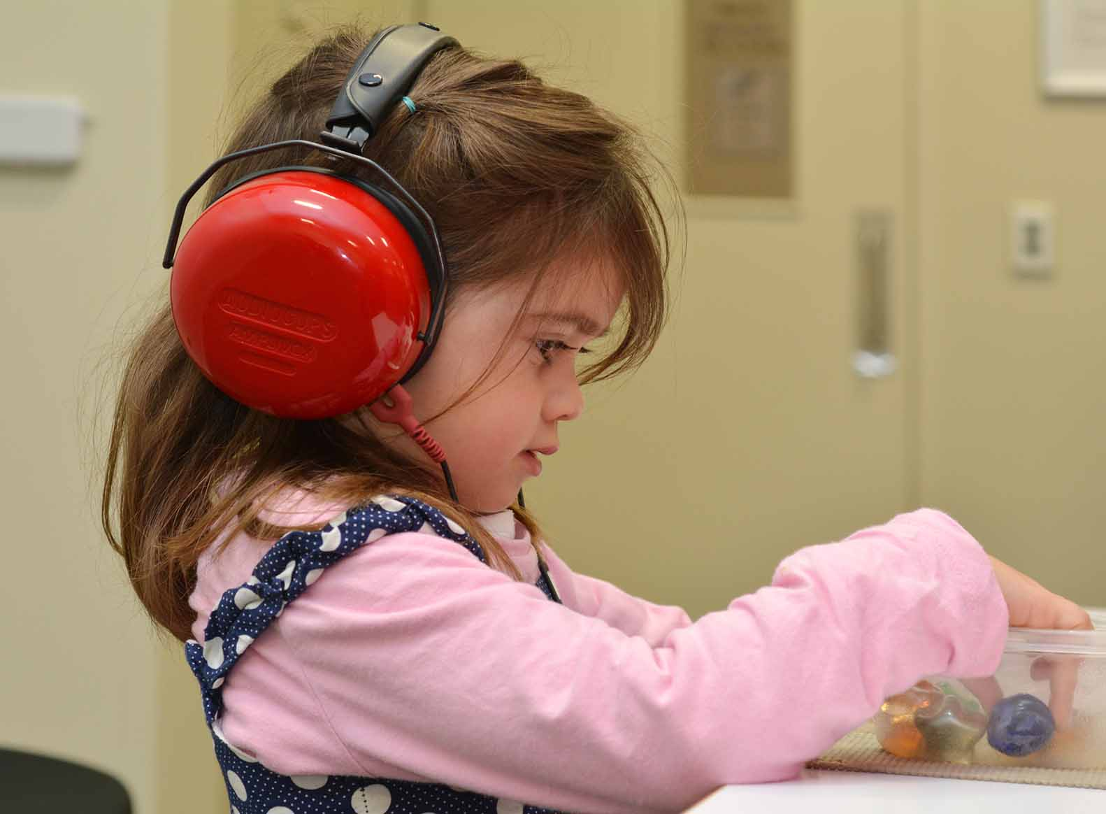 girl wearing ear defenders and playing with toys text auditory sensitivity