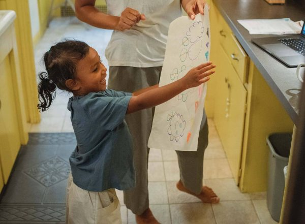 child showing parent drawing