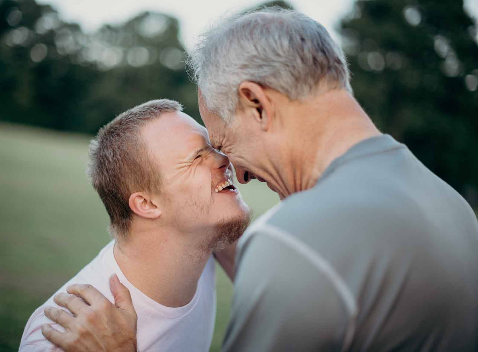 father and son facing each other, smiling, and putting foreheads together