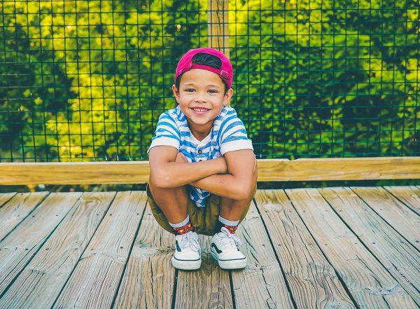 dyspraxic boy crouched down looking at camera