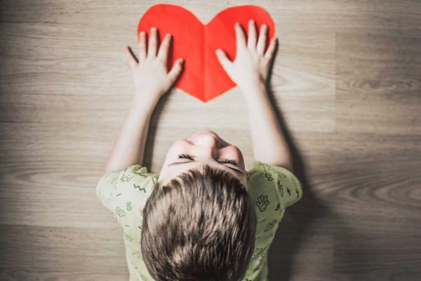 boy holding a larger heart text what is dyspraxia