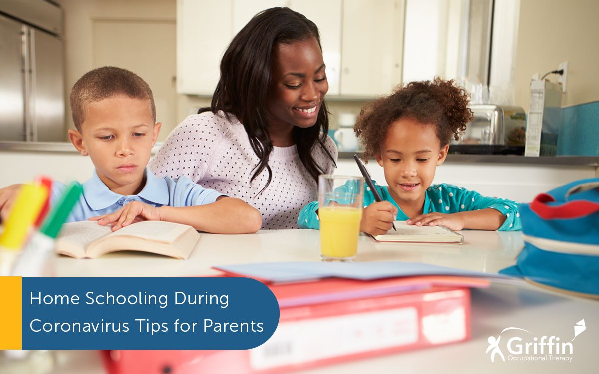 mother sitting with two children homeschooling during coronavirus