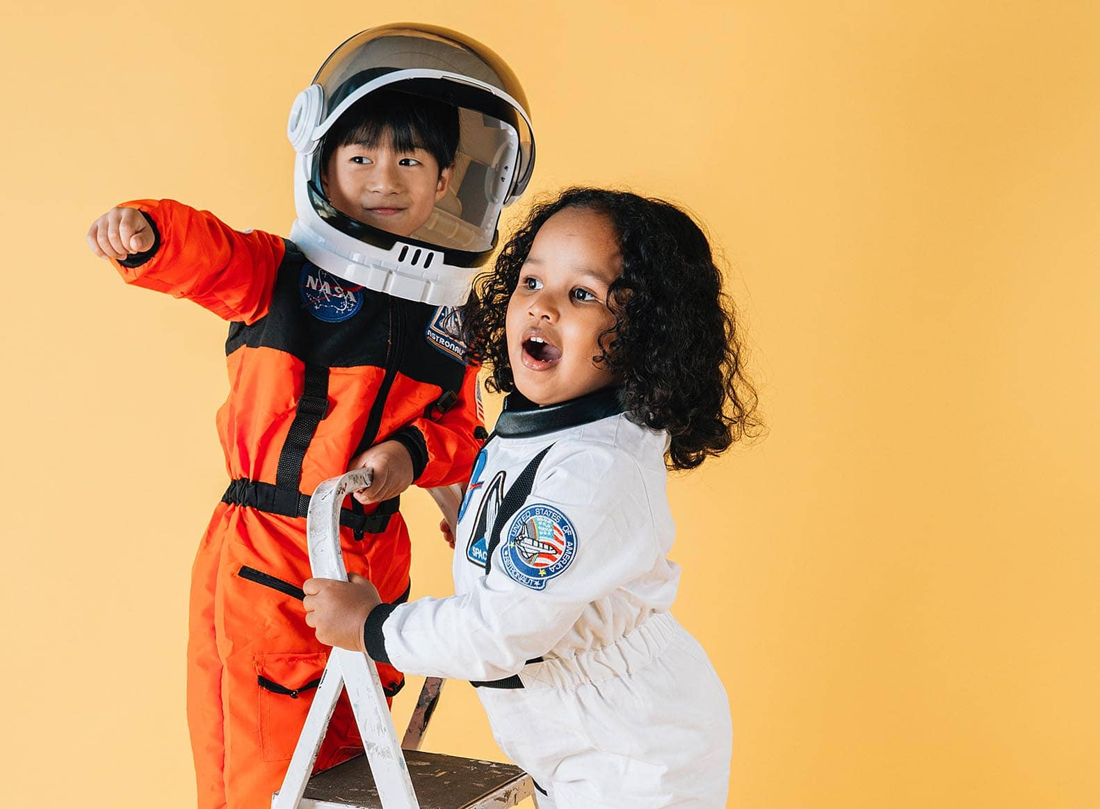 boy and girl in space suits playing