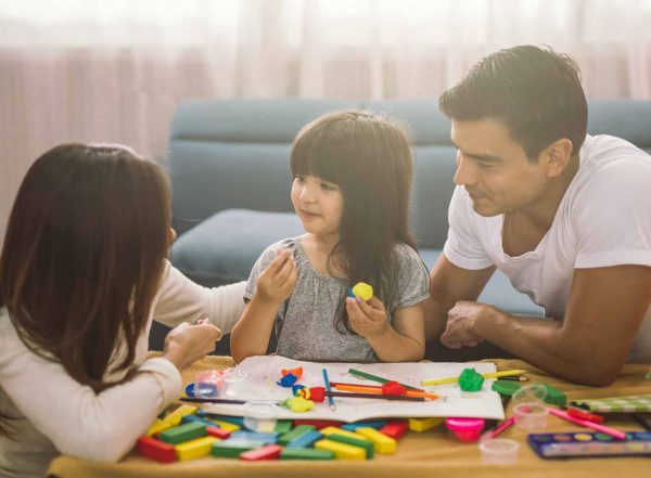 parents sitting at table with daughter who is holding a pompom, pencil grasps and craft on the table text motor skills for handwriting success