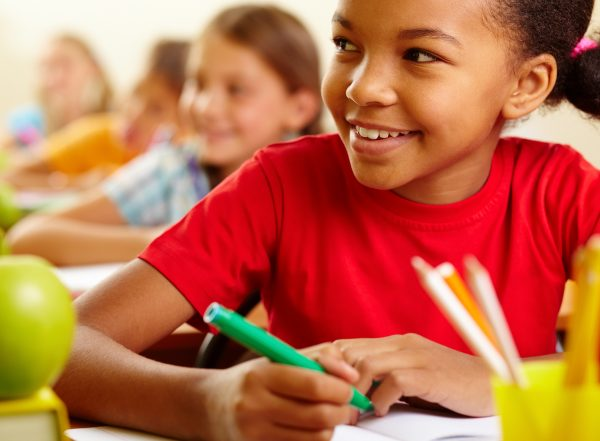 child holding a pen and looking up towards teacher