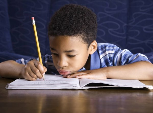 boy writing with immature pencil grasp