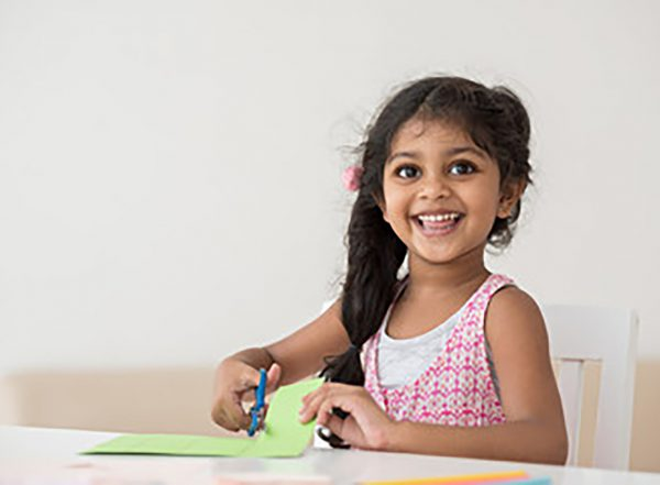 girl cutting paper text supporting scissor skills