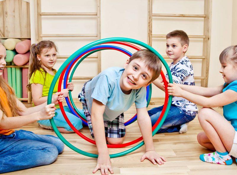boy crawling through hoola hoop text sensory diets