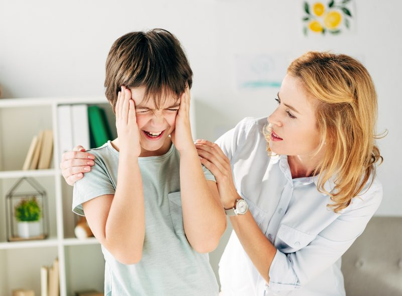 child with hands up to head and mother trying to comfort