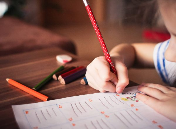 girl writing with immature pencil grasp
